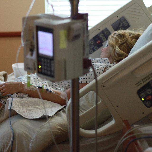 Ljushårig kvinna i en sjukhussäng